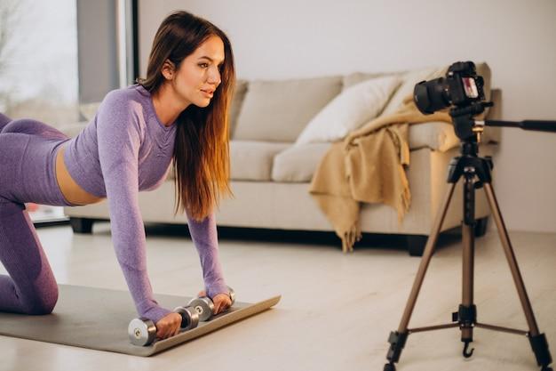 Frau, die von zu hause aus trainiert und videos macht