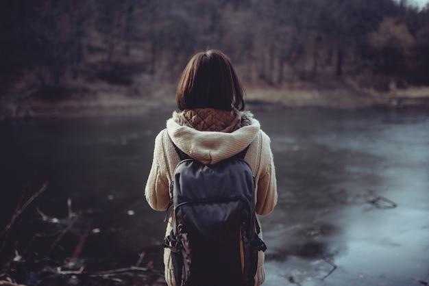 Frau, die vor dem gebirgssee steht