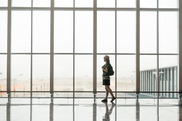 Frau, die vor einem riesigen glasfenster mit einem hut