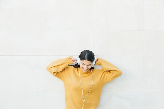 Frau, die vor hörender musik der wand auf kopfhörern steht