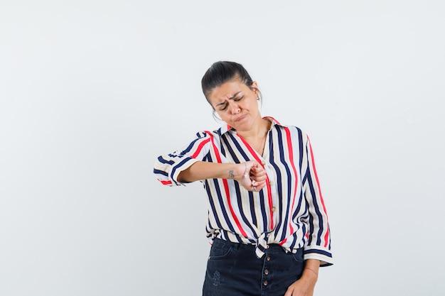 Frau, die vorgibt, in hemd, rock und nachdenklich auf die uhr an ihrem handgelenk zu schauen.