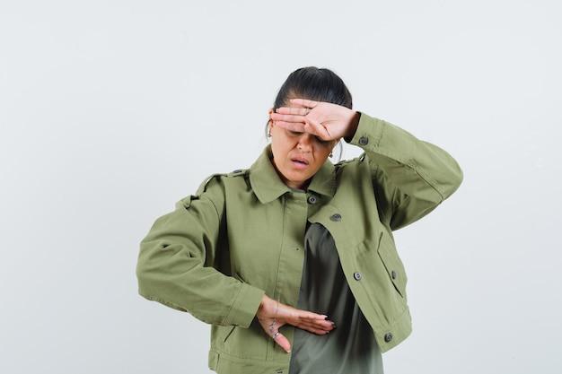 Frau, die vorgibt, uhr auf ihrem handgelenk in jacke, t-shirt zu schauen und vergesslich auszusehen