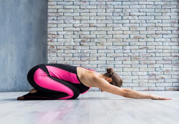 Frau, die vorwärts ihre arme beim handeln von yoga ausdehnt