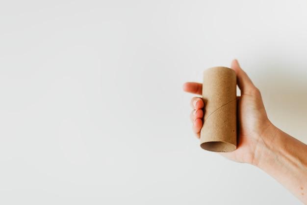 Frau, die während der coronavirus-pandemie eine leere toilettenpapierrolle hält
