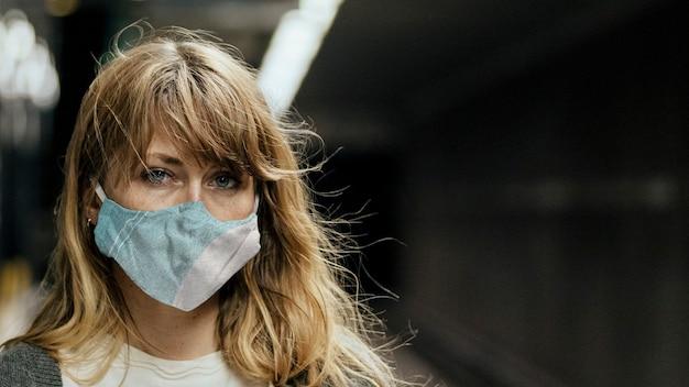 Frau, die während der coronavirus-pandemie eine maske trägt, während sie auf den zug wartet