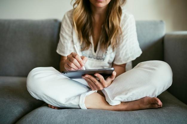 Frau, die während der coronavirus-quarantäne einen stift verwendet, der auf einem digitalen tablet schreibt