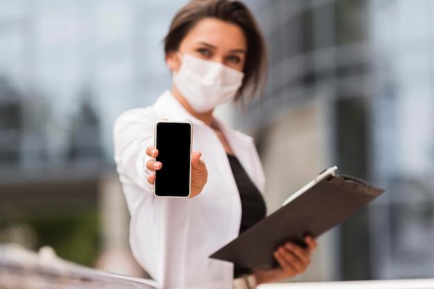 Frau, die während der pandemie im freien arbeitet, zeigt smartphone beim halten des notizblocks