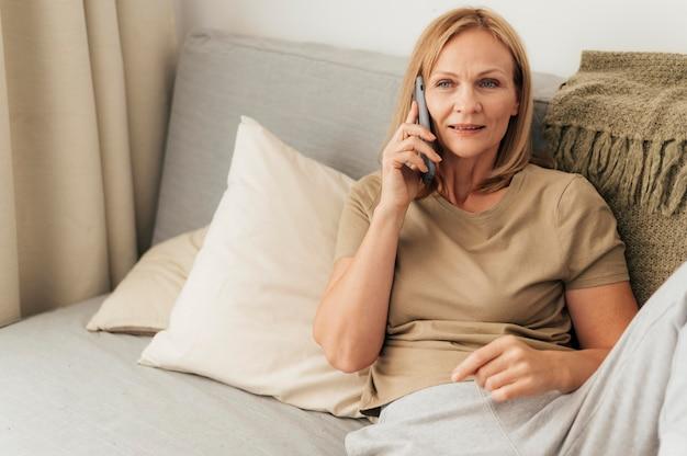 Frau, die während der quarantäne zu hause am telefon spricht