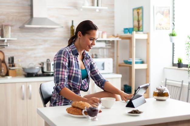 Frau, die während des frühstücks in der küche auf einem tablet-pc surft und eine tasse grünen tee hält