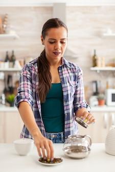 Frau, die während des frühstücks zu hause aromastoffe für die zubereitung von heißem tee verwendet