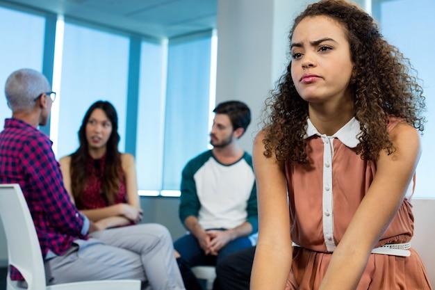Frau, die während des kreativen geschäftsteams hinter im büro weint