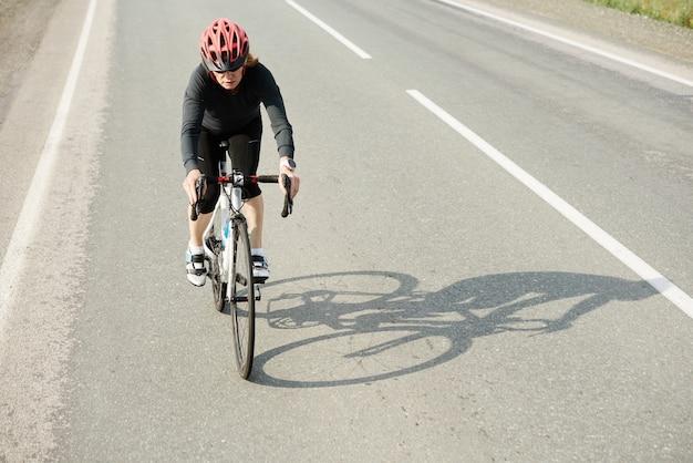 Frau, die während des sporttrainings auf der sonnigen straße oder der autobahn des landsommers radfährt