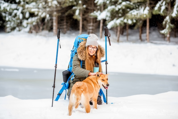 Frau, die während des winterwanderns eine pause macht und ihren hund in den schneebedeckten bergen in der nähe des sees und des waldes streichelt