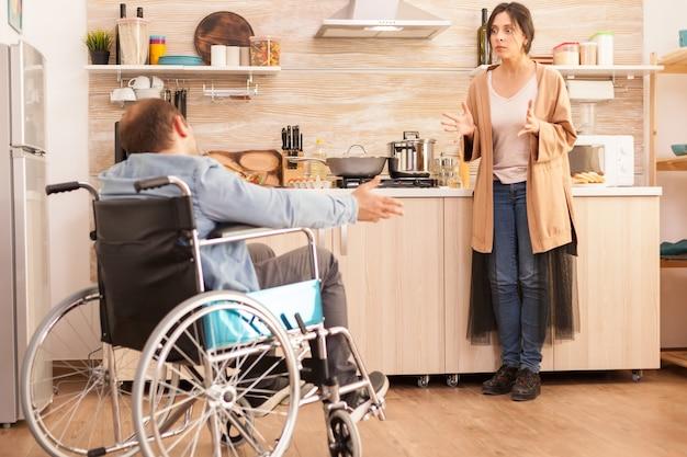Frau, die während eines streits über ihre beziehung in der küche wütend auf einen behinderten mann im rollstuhl schaut. behinderter, gelähmter, behinderter mann mit gehbehinderung, der sich nach einem unfall integriert.