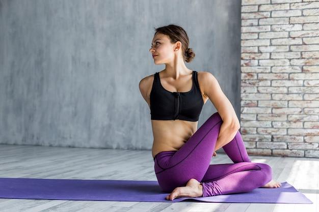 Frau, die während ihrer yogasitzung sich verdreht