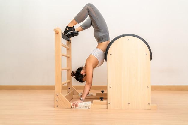 Frau, die während ihres gesundheitstrainings handstand auf pilates-leiter-fassmaschine macht