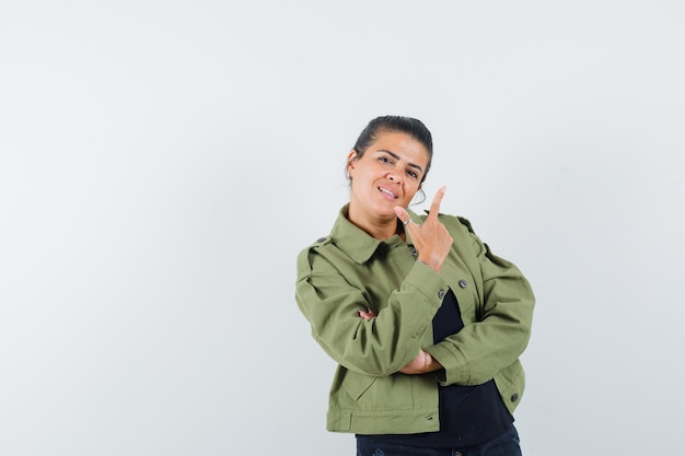 Frau, die waffengeste in jacke, t-shirt zeigt und zuversichtlich schaut.
