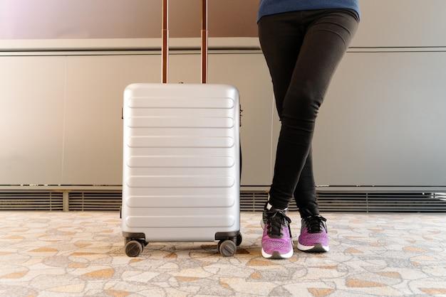 Frau, die warteflug des nahen reisegepäcks im modernen anschluss steht