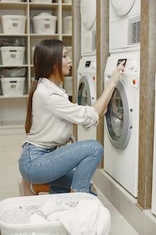 Frau, die waschmaschine benutzt, die die wäsche tut. junge frau bereit, kleidung zu waschen. innenraum, waschprozesskonzept