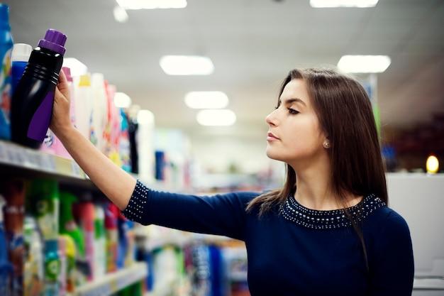 Frau, die waschmittel im supermarkt wählt