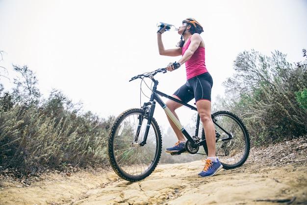 Frau, die wasser auf einem fahrrad trinkt