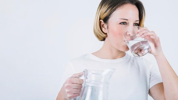 Frau, die wasser auf weißem hintergrund genießt