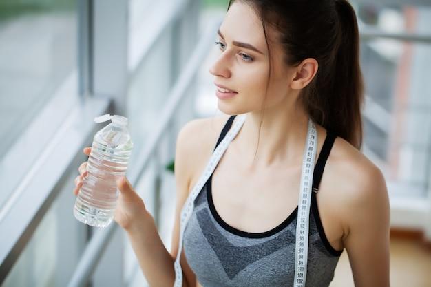 Frau, die wasser im fitnessstudio nach dem training trinkt.