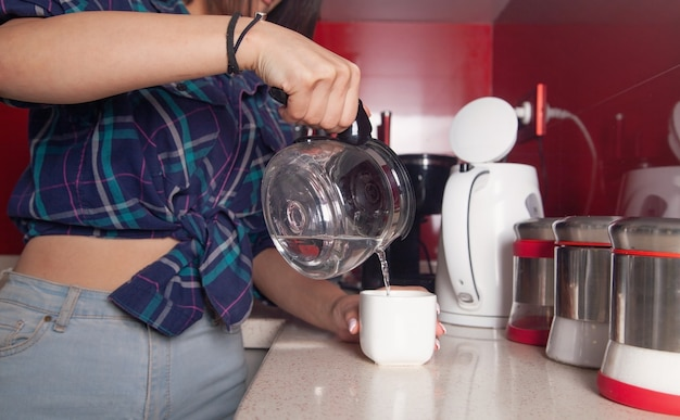Frau, die wasserkocher hält und wasser in die tasse gießt. getränk zubereiten Premium Fotos