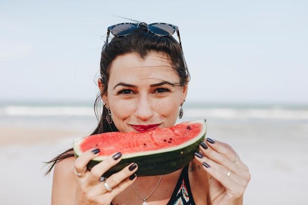 Frau, die wassermelone am strand isst