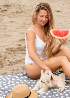 Frau, die wassermelone am strand mit hund isst