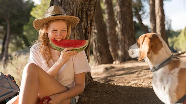 Frau, die wassermelone und hund isst, die neben ihr sitzen
