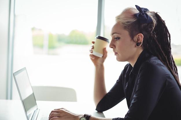 Frau, die wegwerfkaffeetasse bei der anwendung des laptops hält
