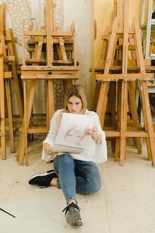 Frau, die weibliche skizze auf gewundenem zeichnungsbuch betrachtet