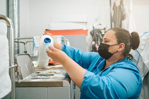 Frau, die weichspüler und waschmittel in die industriewaschmaschine einsetzt