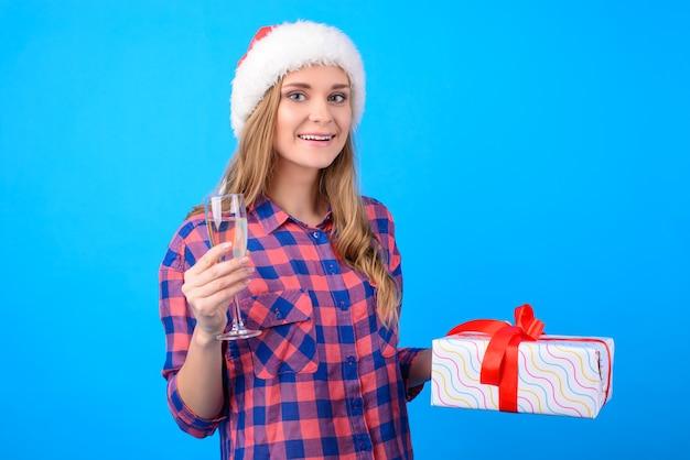 Frau, die weihnachten hält, hält ein glas champagner und eine geschenkschachtel