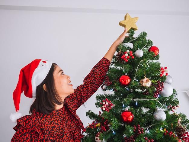 Frau, die weihnachtsbaum mit sternen verziert