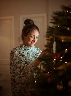 Frau, die Weihnachtsbaum verziert
