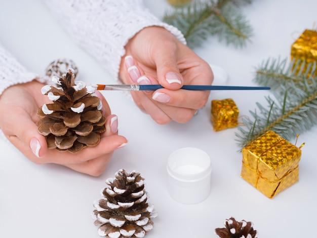 Frau, die weihnachtsdekorationen mit kiefernkegeln macht