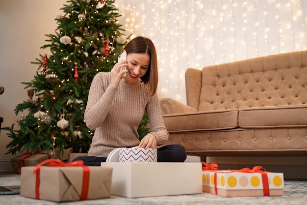 Frau, die weihnachtsgeschenk einwickelt und am telefon spricht, während sie in weihnachten sitzt
