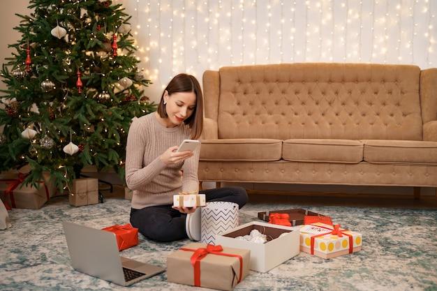 Frau, die weihnachtsgeschenk einwickelt und bilder am telefon beim sitzen in weihnachten macht
