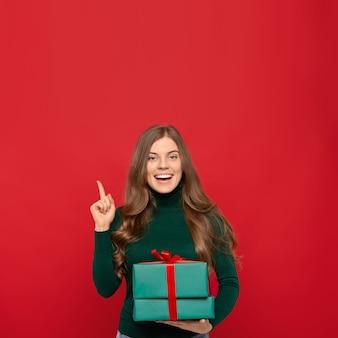 Frau, die weihnachtsgeschenk hält und mit finger oben zeigt