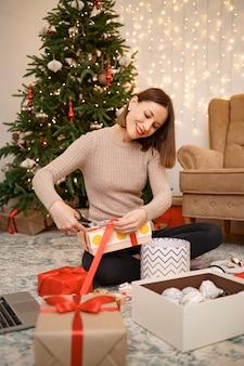 Frau, die weihnachtsgeschenk verpackt, während sie auf dem teppich im wohnzimmer sitzt