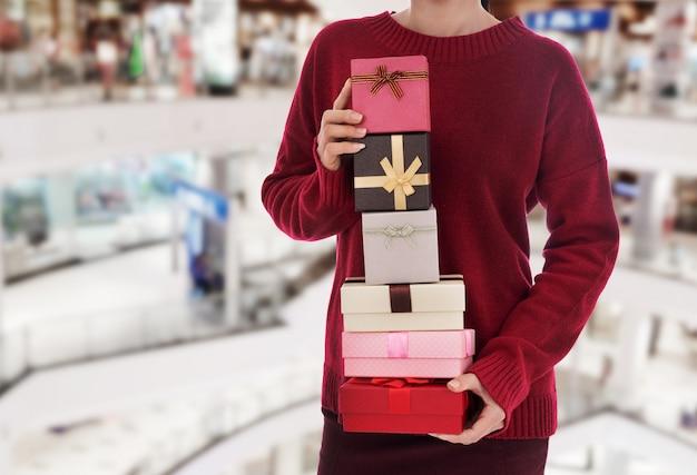 Frau, die weihnachtsgeschenkbox am mall hält