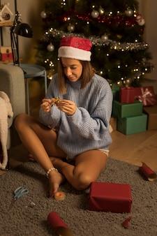 Frau, die weihnachtsgeschenke einwickelt, während sie weihnachtsmütze trägt