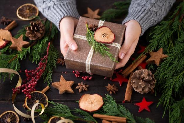 Frau, die weihnachtsgeschenke hält, legte auf einen hölzernen tischhintergrund.