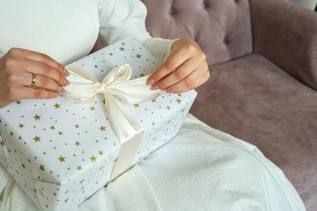 Frau, die weihnachtsgeschenke unter baumnahaufnahme einwickelt.
