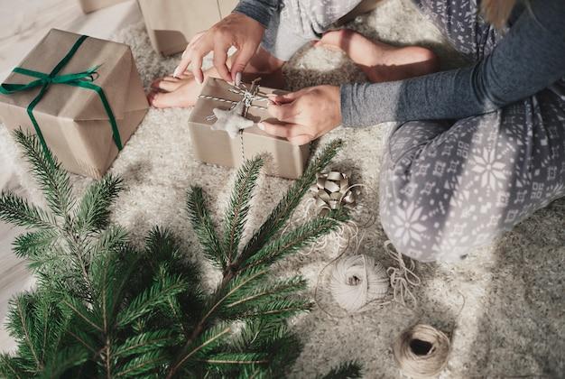 Frau, die weihnachtsgeschenke zu hause macht