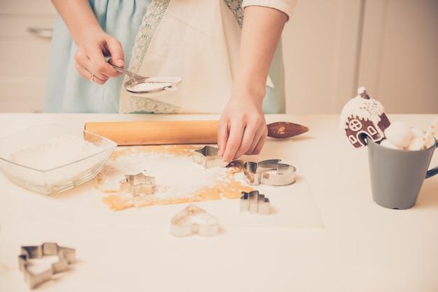 Frau, die weihnachtslebkuchen in der küche vorbereitet