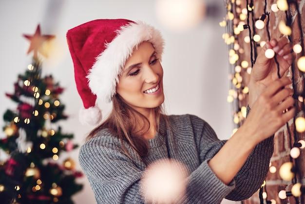 Frau, die weihnachtslichter zu hause hängt