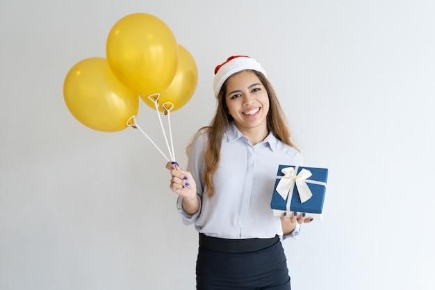Frau, die weihnachtsmann-hut trägt und geschenkbox und ballone hält